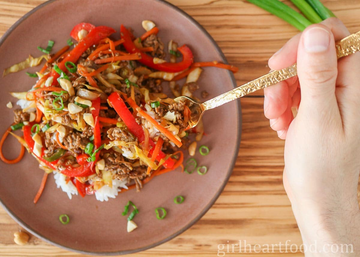 Hand holding a fork, scooping up stir-fry from a plate of it.