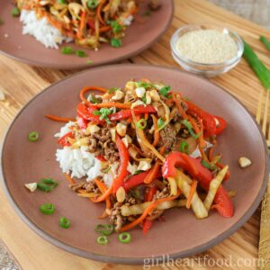 Ground beef stir-fry & rice on a plate, in front of another plate of stir fry & sesame seeds.