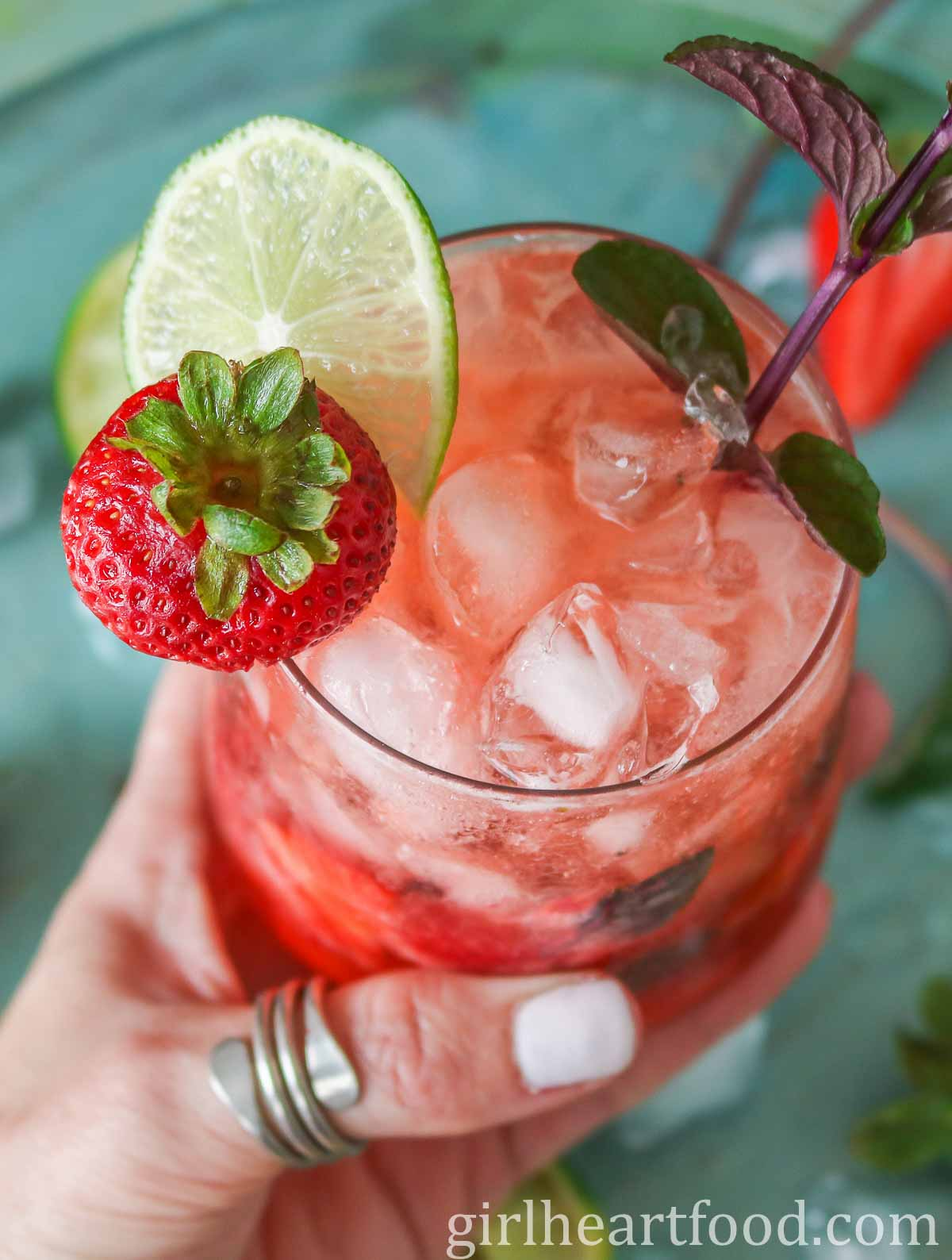 Hand holding a strawberry mocktail.