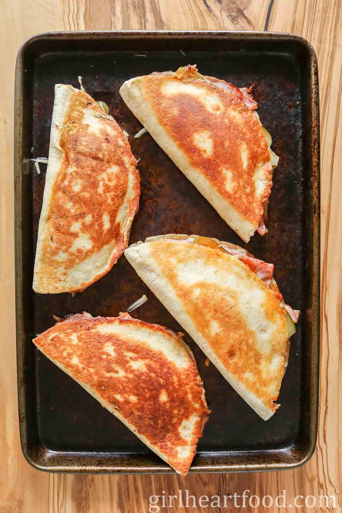 Four crispy quesadillas on a sheet pan.