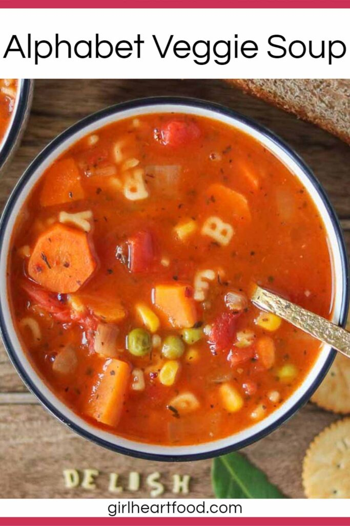 Bowl of vegetable alphabet soup with a spoon in the soup.