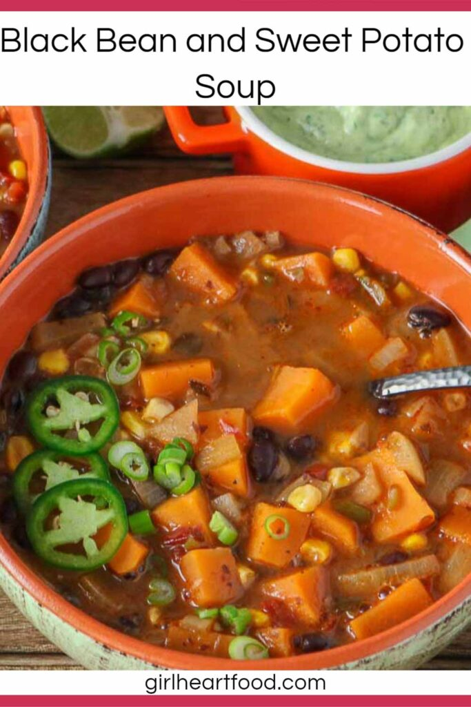 Bowl of black bean sweet potato soup with a dish of avocado lime crema behind it.