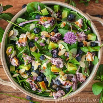 Dish of blueberry spinach salad drizzled with vinaigrette.
