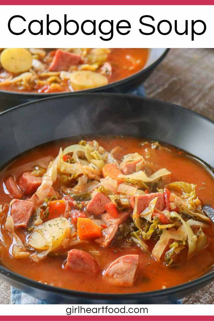 Two bowls of cabbage soup with sausage and potatoes, one bowl in front of the other.