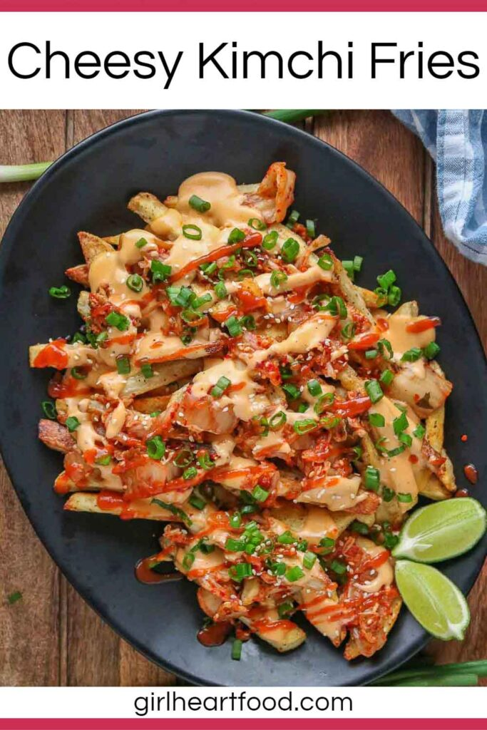 Cheesy kimchi fries and two lime wedges on a black platter next to green onion.