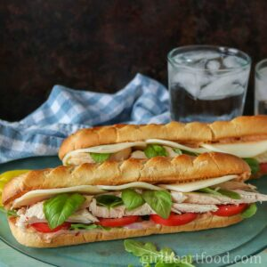 Two chicken baguette sandwiches in front of a tea towel and glass of water.