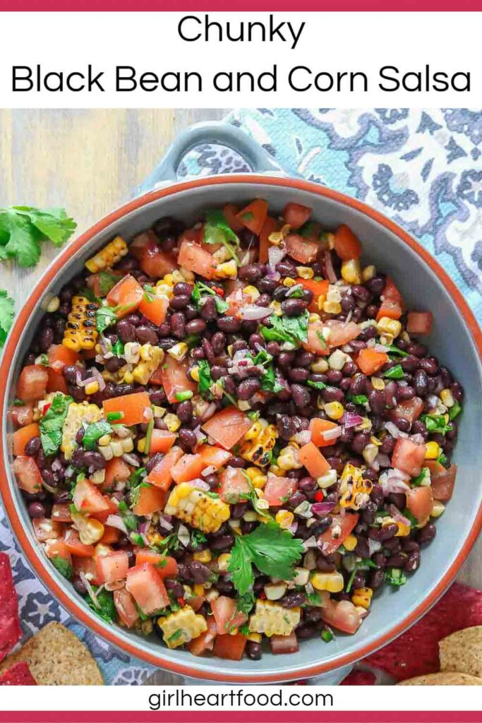 Dish of black bean and corn salsa, sitting on a tea towel, next to some tortilla chips.
