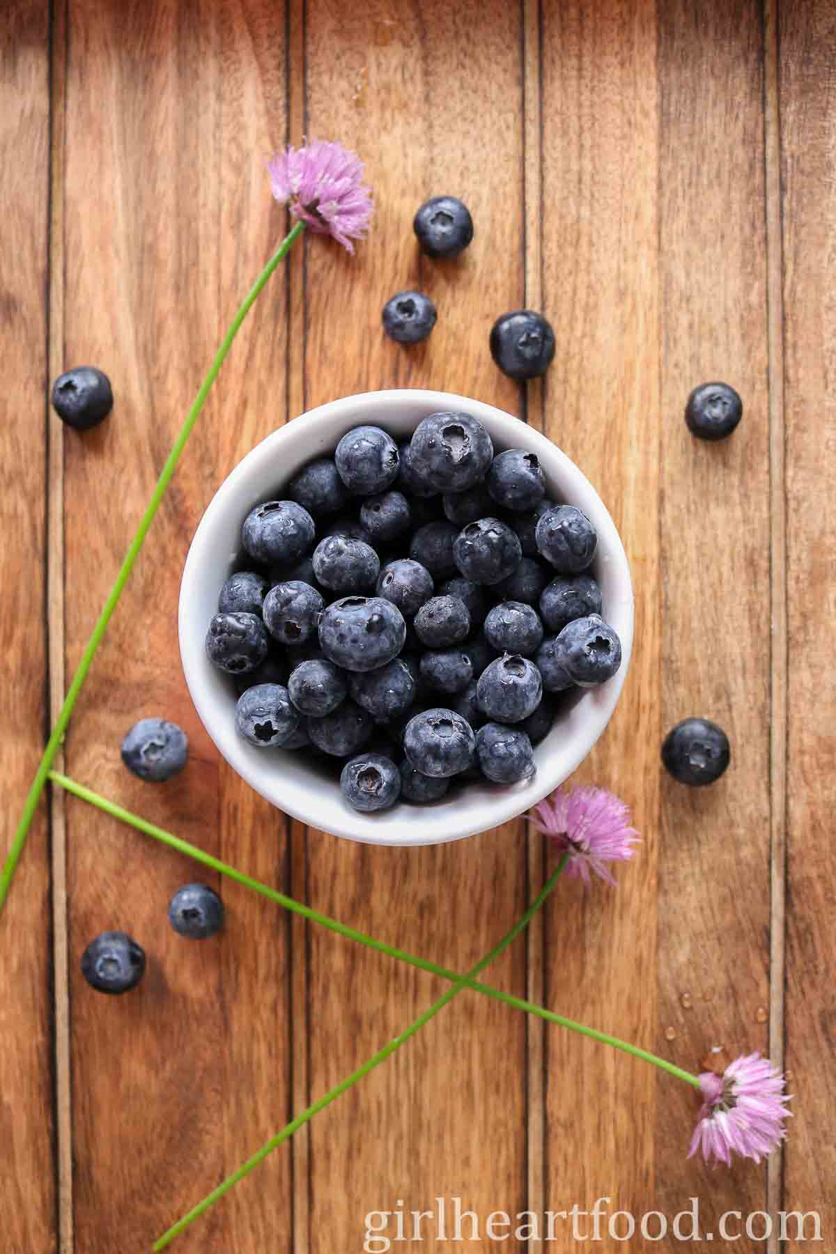 Small dish of fresh blueberries next to more blueberries and chives.