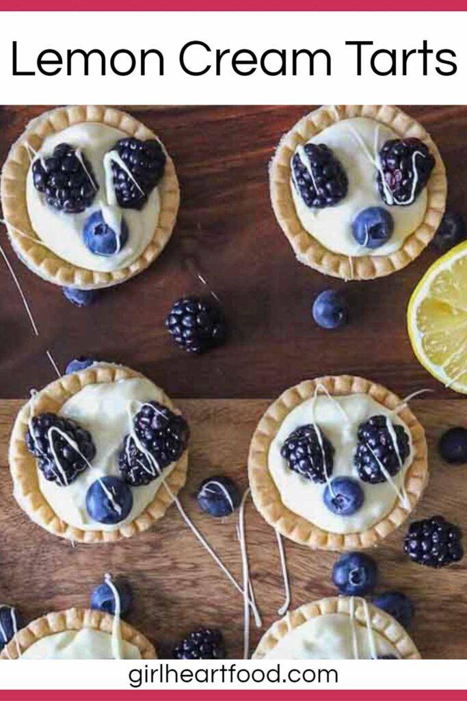 Six lemon cream tarts garnished with fresh berries.