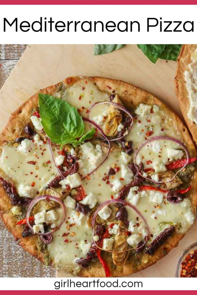 Mediterranean pizza on cauliflower crust garnished with fresh basil.