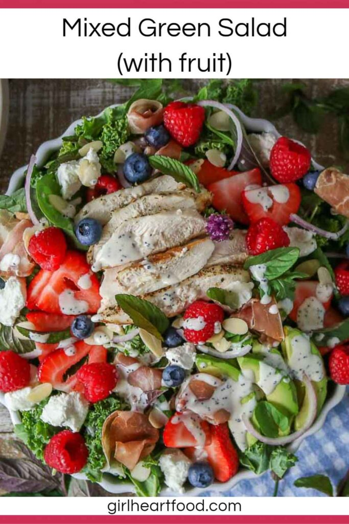 Bowl of mixed green salad with fruit, chicken, prosciutto and poppy seed dressing.