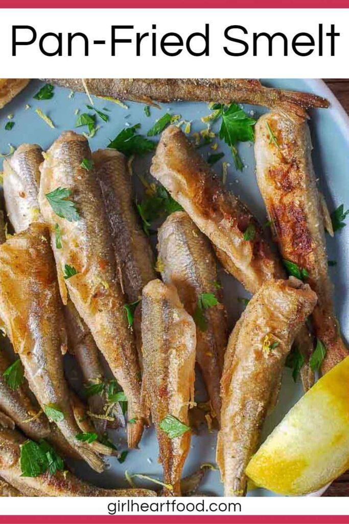 Crispy smelt fish and a lemon wedge on a blue plate.