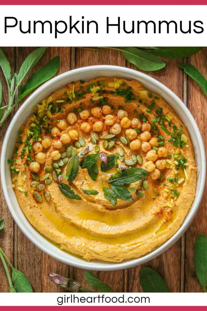 Bowl of pumpkin hummus garnished with toppings and surrounded by fresh sage.