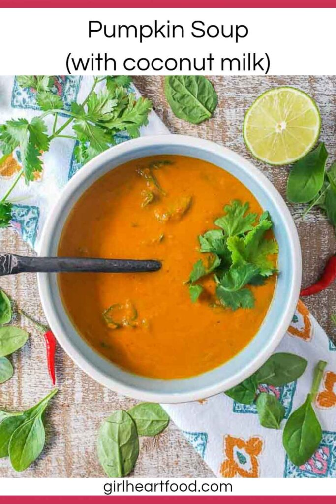 Bowl of pumpkin soup next to spinach, lime, chili peppers and cilantro.
