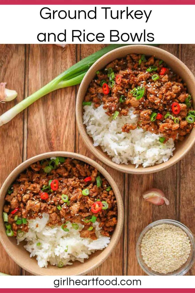 Two ground turkey and rice bowls next to green onion, garlic cloves and sesame seeds.