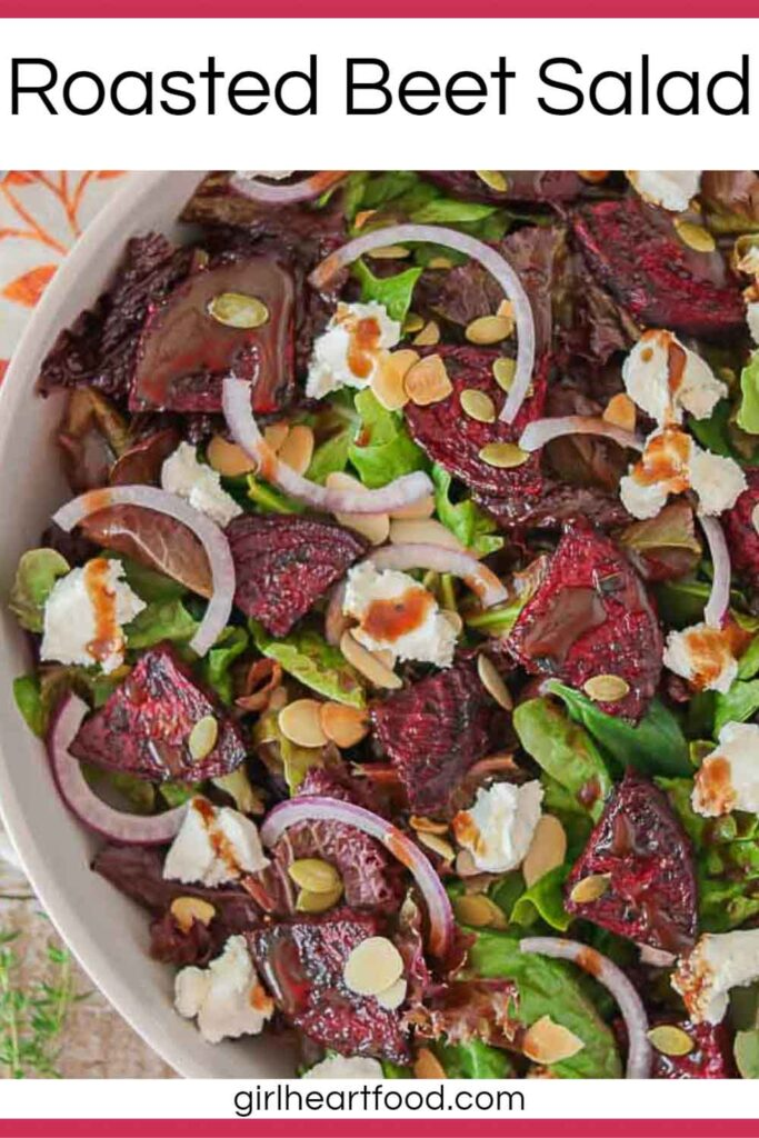 Close-up of a dish of roasted beet salad with balsamic vinaigrette drizzled over top.