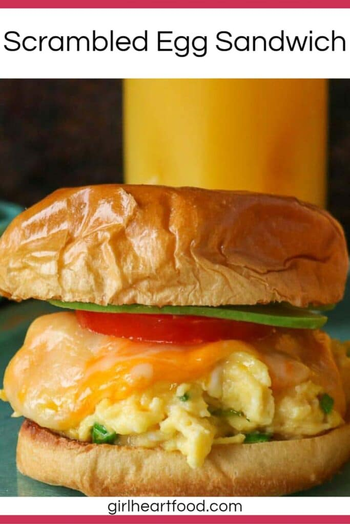 Cheesy scrambled egg sandwich with a glass of orange juice behind it.