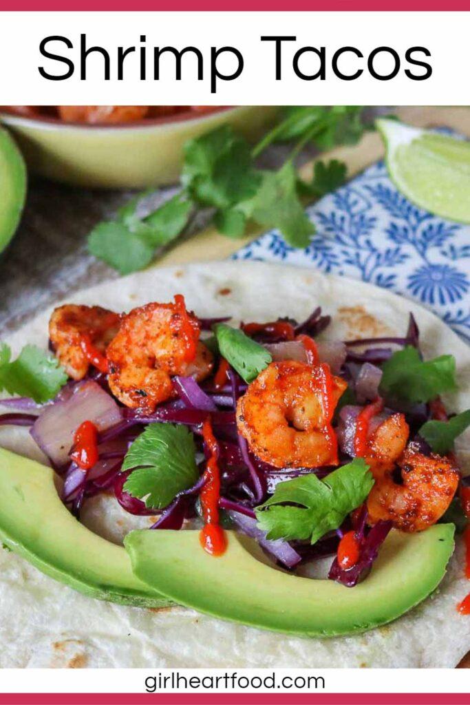 Shrimp taco garnished with slaw, avocado, cilantro and hot sauce.
