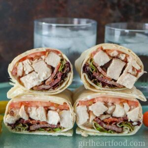 Four turkey bacon wraps in front of two glasses of water.