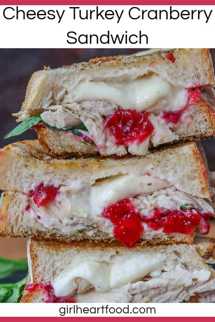Close-up of a stack of three cheesy turkey cranberry sandwich halves.