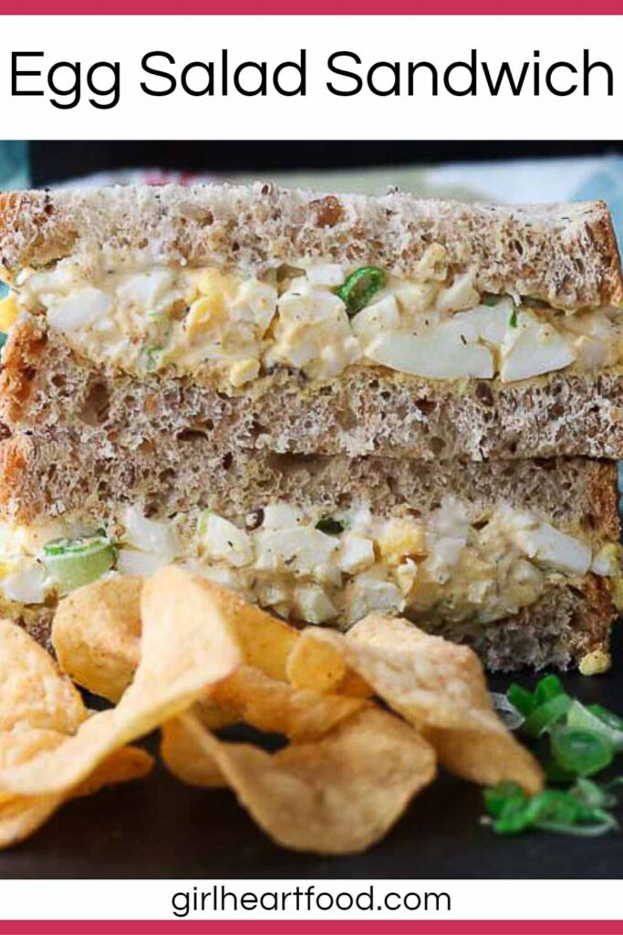 Stack of two halves of a classic egg salad sandwich next to potato chips.