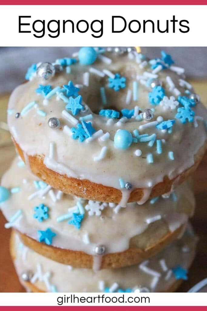 Close-up of a stack of three baked eggnog donuts with glaze and festive sprinkles.