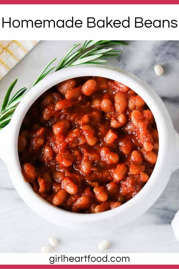 Bowl of homemade baked beans next to fresh rosemary and dried beans.