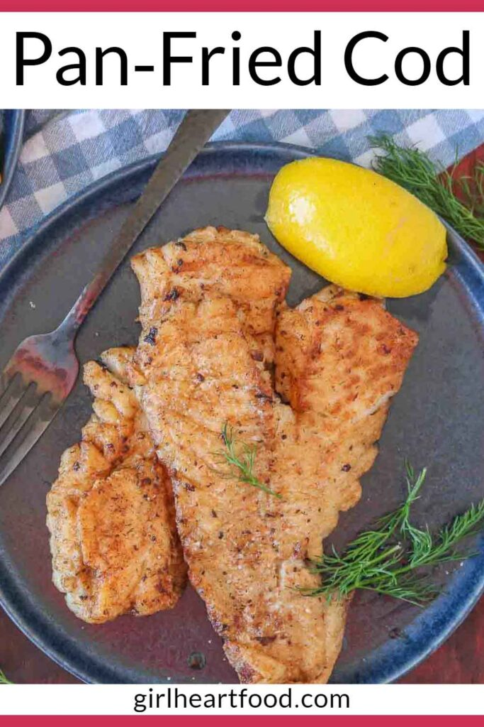 Pan-fried cod fillets with dill and a lemon wedge on a dark blue plate.