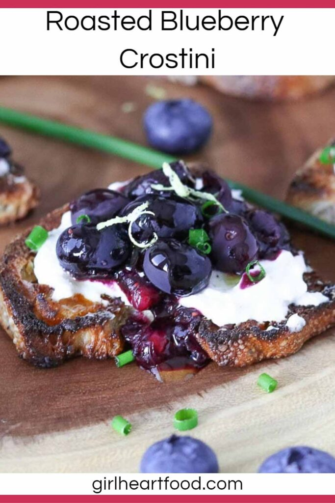Roasted blueberry and goat cheese crostino next to blueberries and chives.