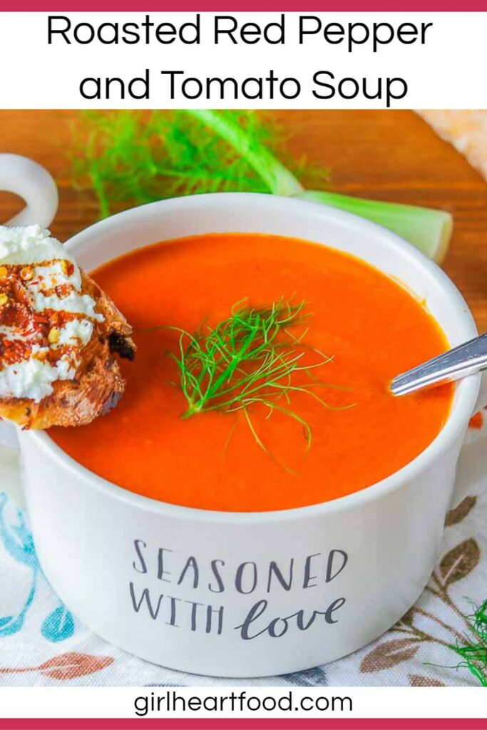 Bowl of roasted red pepper tomato fennel soup with a crostino resting on the bowl.