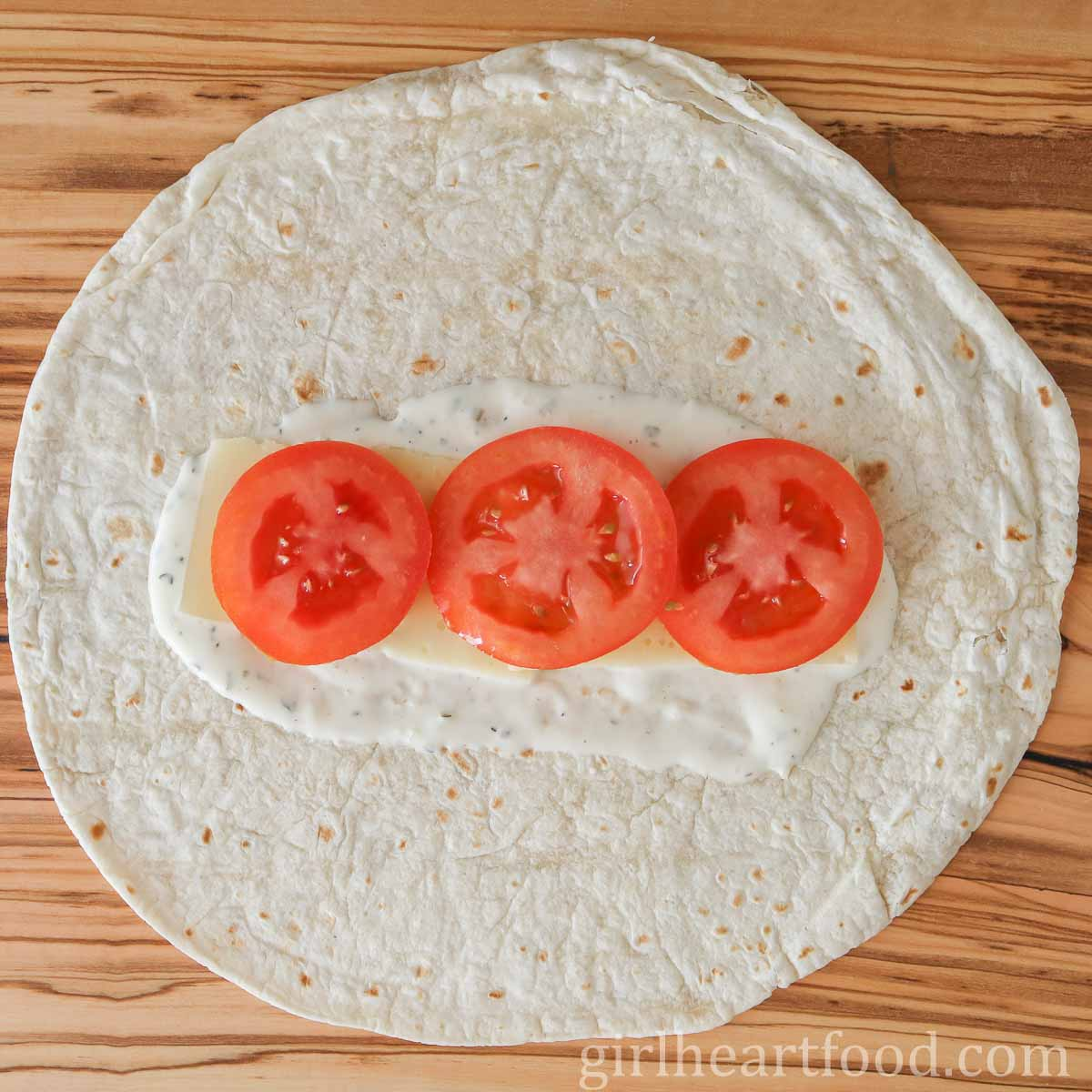 Ranch dressing, cheese and sliced tomato on a tortilla.