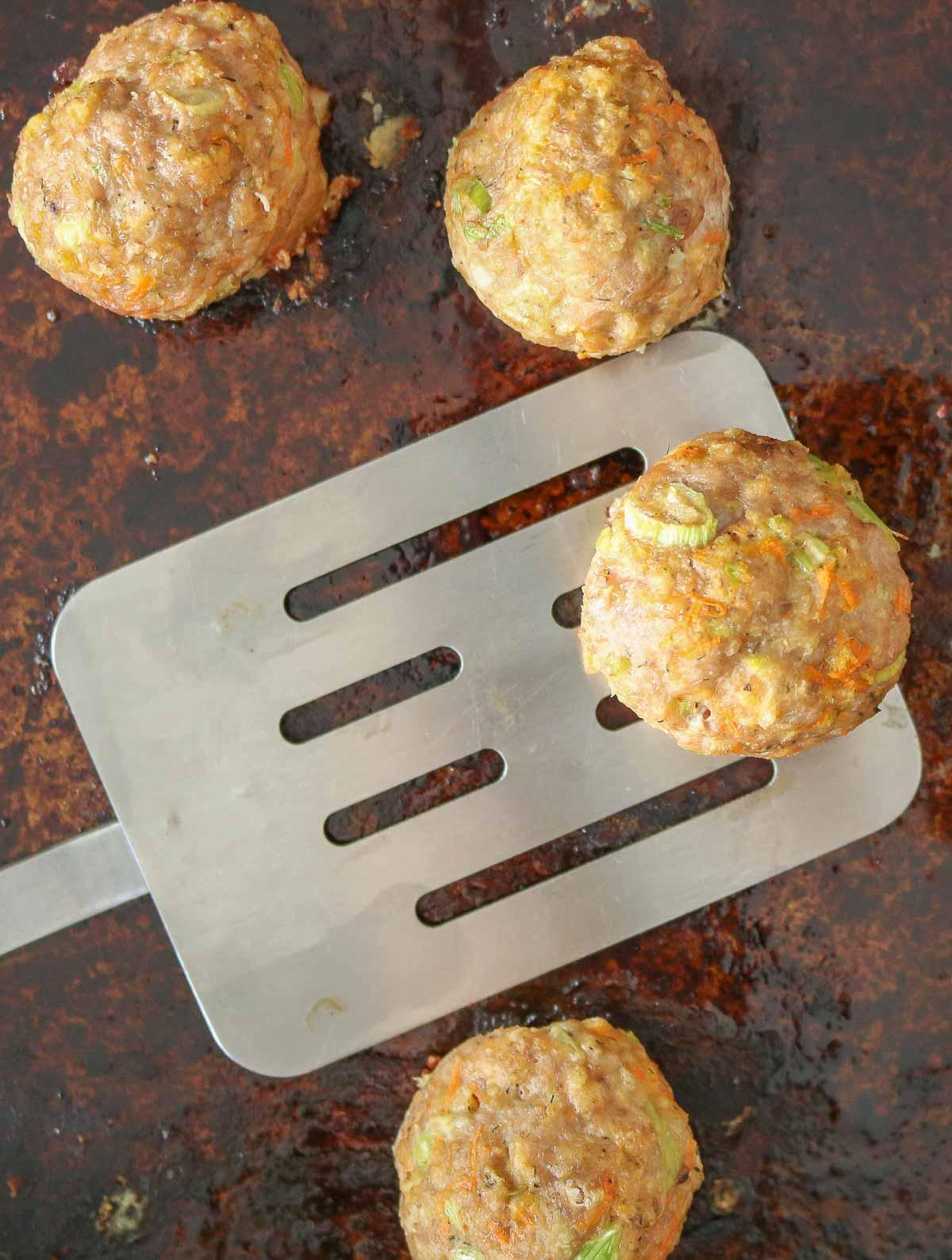 Spatula picking up a turkey meatball from a sheet pan.