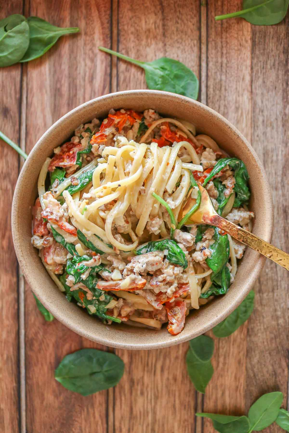 Bowl of ground turkey pasta with a forkful of pasta resting over top.