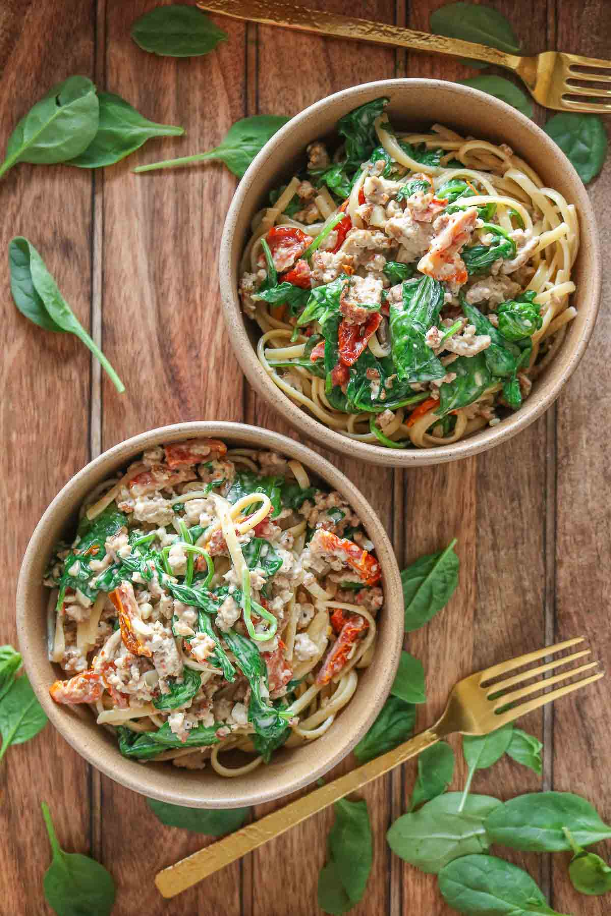 Two bowls of ground turkey pasta next to spinach and forks.