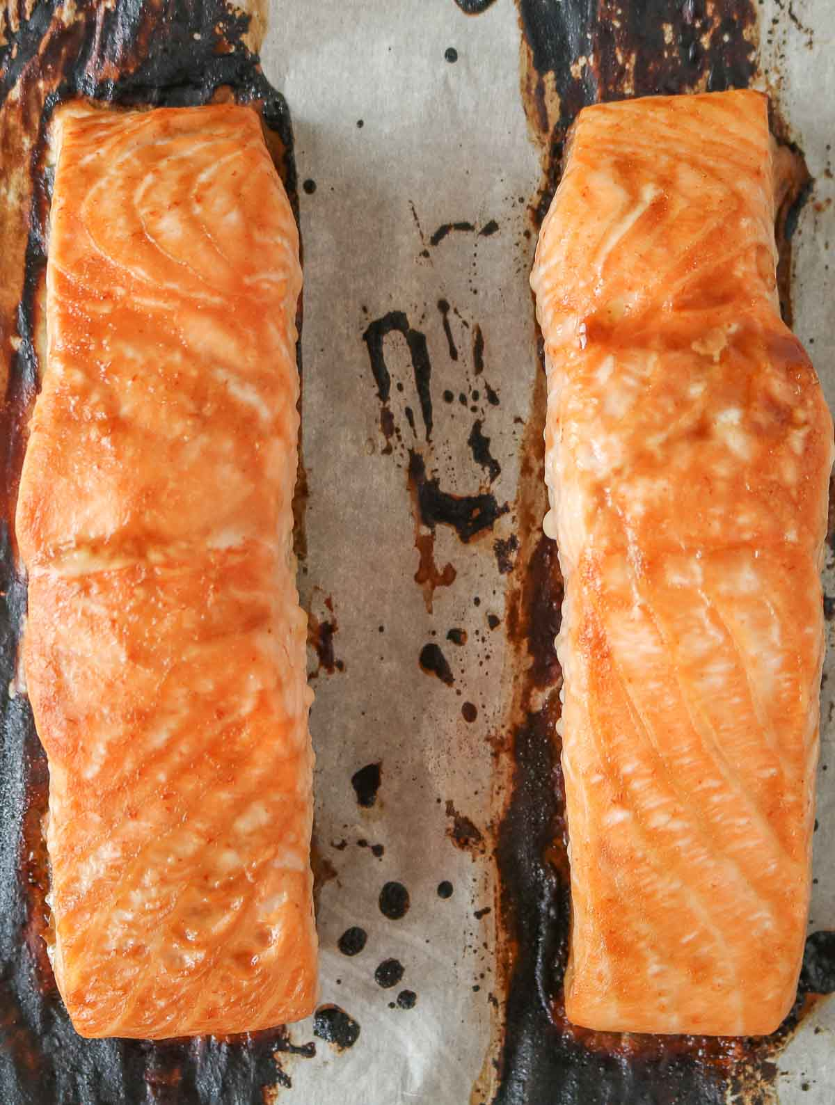 Two glazed salmon fillets after baking.