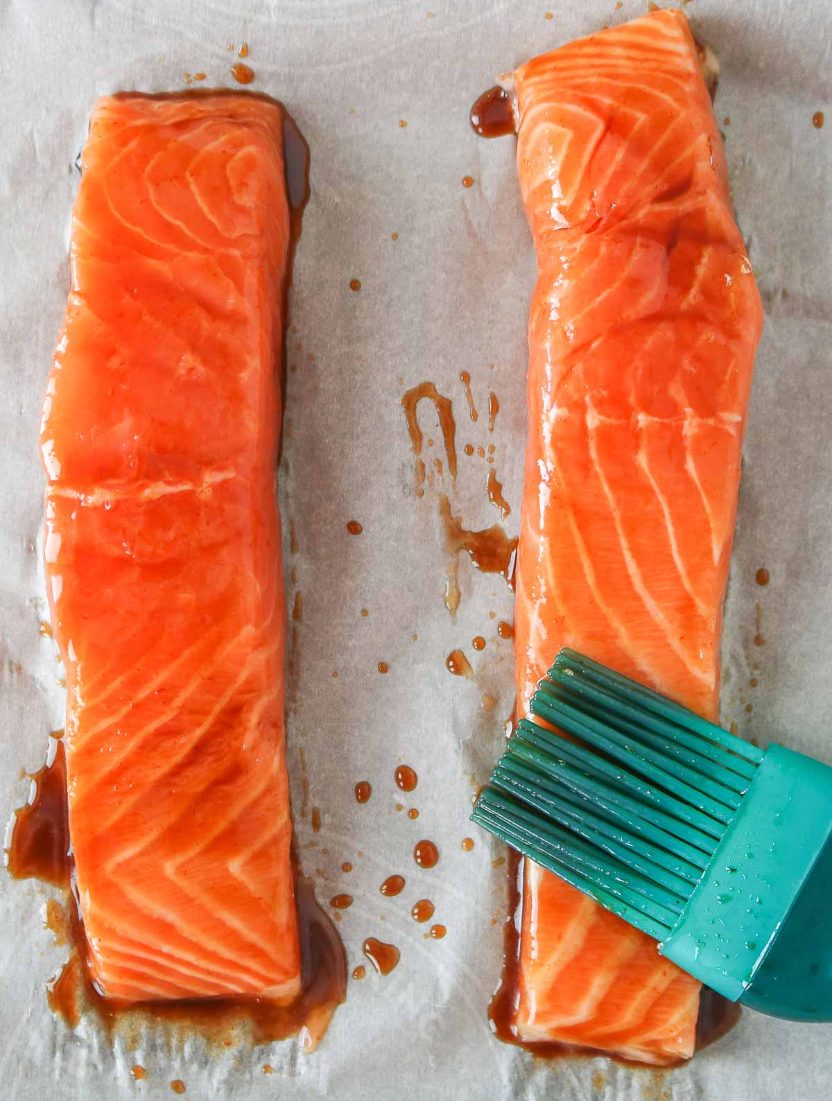 Two uncooked salmon fillets brushed with a soy sauce mixture before baking.